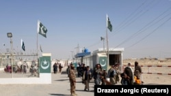 Pakistani soldiers keep guard as citizens return from Afghanistan at the border-crossing town of Chaman in the southwestern Balochistan province.