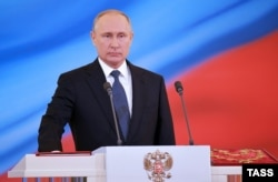 Putin takes the oath of office on a copy of the Russian Constitution.