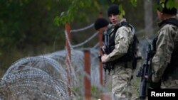 Members of Georgia's Special Forces Police secure an area near wire barricades erected by Russia in the village of Dvani.