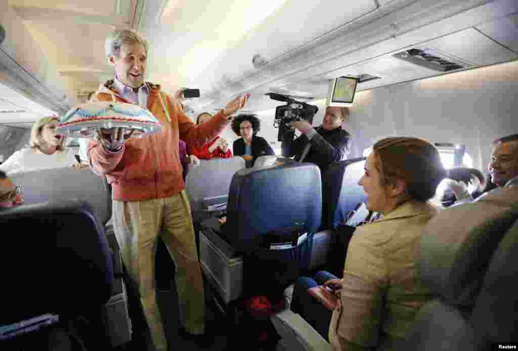 U.S. Secretary of State John Kerry presents a birthday cake to traveling CBS correspondent Margaret Brennan on his flight from Kabul to Paris. (Reuters/Jason Reed)