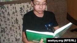 Ученик 7-го класса Дарын Дастанулы читает книгу. Алматы, 10 июня, 2014 года.