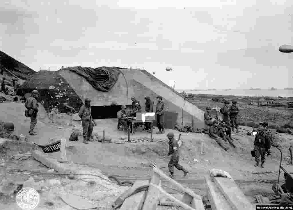 U.S. Army troops congregate around a signal post used by engineers on the site of a captured German bunker overlooking Omaha Beach after the D-Day landings near Saint Laurent sur Mer June 7, 1944