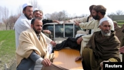 Relatives on February 21 transport the body of an Afghan man killed after an air strike in Nangarhar Province.