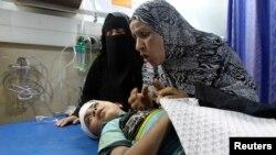 Газа - палестиналык аял Израилдин аба соккусунан жарат алып, ооруканада жаткан уулунун жанында, Газа шаары, 4-август, 2014.