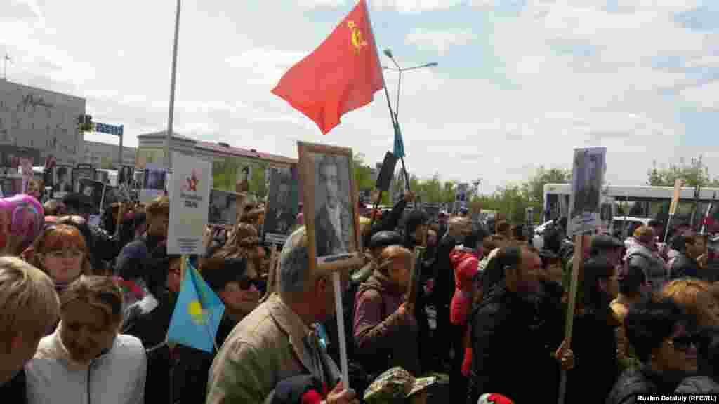 Астанада «Мәңгілік полк» шеруіне шыққандар совет кезіндегі және Қазақстан туларын ұстап тұр.