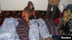 امرأة تنوح الى جانب جثث اطفال قتلتهم صواريخ اطلقت من سوريا على بلدة عرسال.