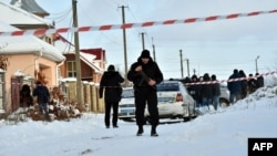 An armed policeman stands guard as police experts examine the scene of the incident in the small town of Knyazichi, some 30 kilometers east of Kyiv, on December 4.