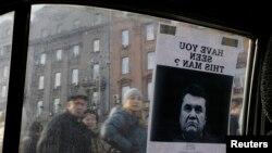 """Киевдин Көз карандысыздык аянтында баррикаданын бөлүгү катары пайдаланылган унаанын терезесинде В.Януковичтин сүрөтү """"Издөө жарыяланды"""" деген сөздөр менен коштолуп тагылып турат. 24.2.2014."""