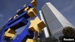Здание Европейского Центробанка с установленным рядом изображением логотипа единой европейской валюты - евро