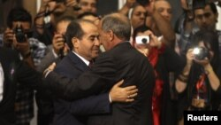 Liwiýada häkimiýetiň Milli assambleýa geçirilmeginden soň, Milli geçiş geňeşiniň başlygy Mustafa Abdel Jalil (sagda), uruş döwrüniň premýer-ministri Mahmud Jibril bilen gujaklaşýar. 8-nji awgust, 2012 ý.