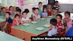 Дети за обеденным столом в детском саду. Иллюстративное фото.