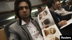 An Iranian hairstylist shows a brochure of official hairstyles in July 2010.