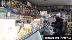 Покупатели у прилавка в небольшом магазине в Алматы.