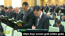 """Türkmenistanyň """"Altyn Asyr"""" döwlet kanalyndan alnan suratda ýygnakda dik durup bellik alýan resmiler görkezilýär (Illýustrasiýa suraty)"""