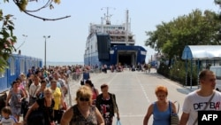 Российские туристы сходят с парома в крымском городе Керчь. Август 2014 года