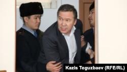 """Обвиняемого в """"разжигании розни"""" Серикжана Мамбеталина выводят из зала суда. Алматы, 20 января 2016 года."""