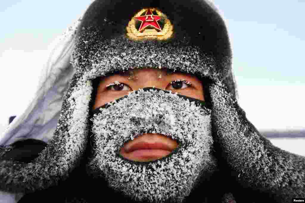 Frost covers the mask and part of the hat of a soldier of China's People's Liberation Army as he stands guard near the border of China and Russia in Heilongjiang Province.(Reuters)