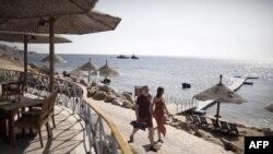 Туристы идут вдоль побережья Красного моря на египетском курорте Шарм-эль-Шейх.