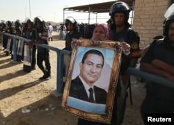 Женщина держит в руках портрет Хосни Мубарака. Каир, 2 июня 2012 года.