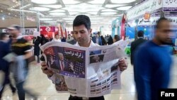 A man reading a newspaper in Tehran.