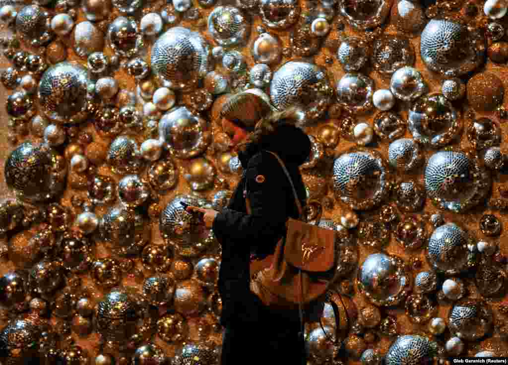 A woman uses her mobile phone as she walks past a shopping mall entrance with Christmas decorations in central Kyiv, Ukraine. (Reuters/Gleb Garanich)