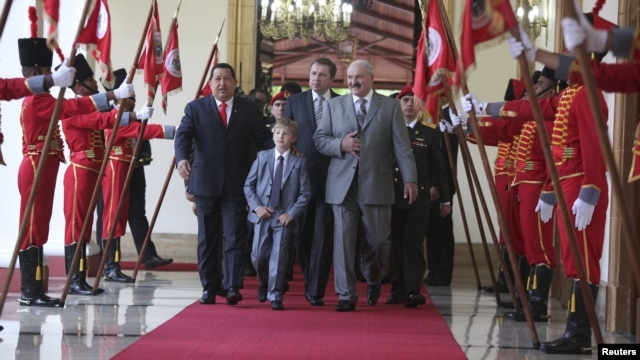 President Hugo Chavez (left) escorts his Belarusian counterpart, Alyaksandr Lukashenka, and the Belarusian president's son, Mykalay, at a welcoming ceremony at Miraflores Palace in Caracas on June 26.