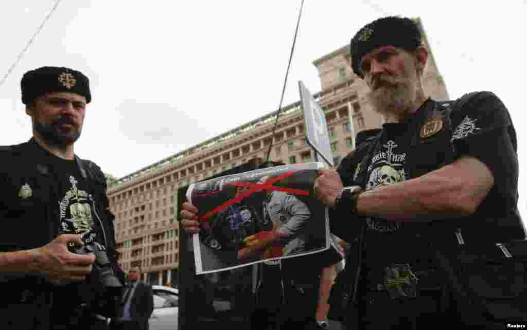An Orthodox believer holds a poster before a protest by gay-rights activists.
