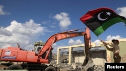 A boy waves a flag as an excavator demolishes walls of the residence of Muammar Qaddafi at the Bab al-Aziziyah complex in Tripoli on October 16.
