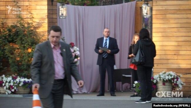 Держохоронець зі значком УДО пересуває фішки на парковці перед ресторанним комплексом