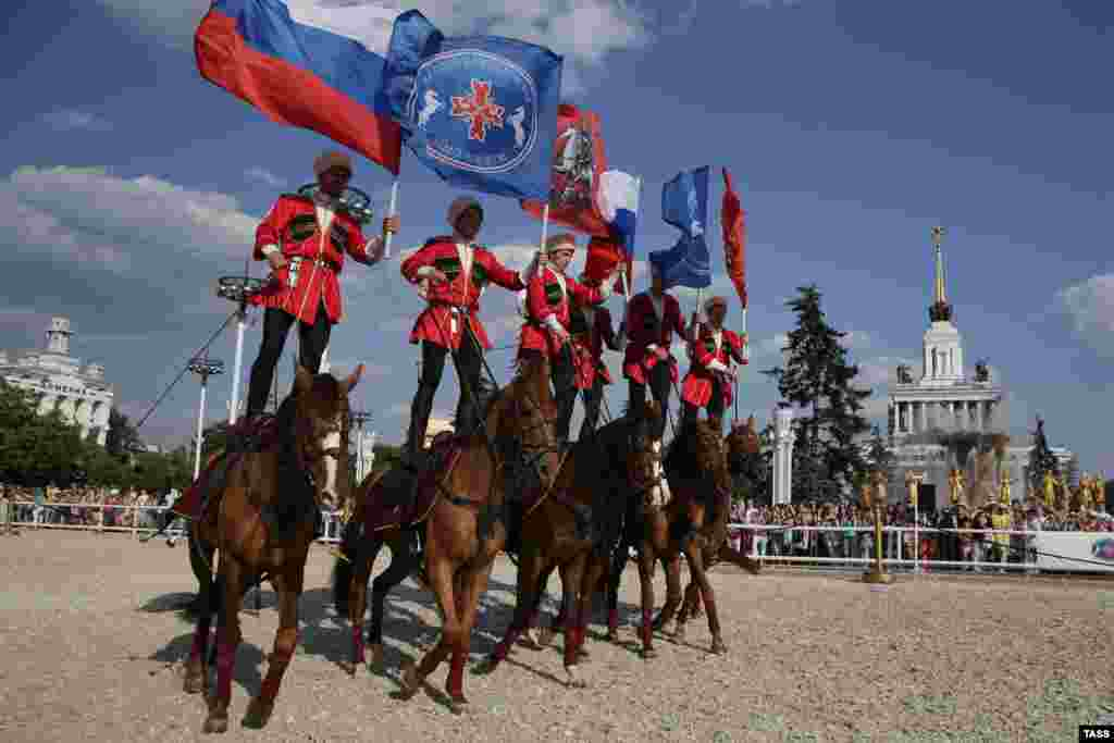Riders from a joint team of the Presidential Regiment Cavalry Escort and the Kremlin Horse Riding School perform during a horse stunt show at the All-Russian Exhibition Center in Moscow. (ITAR-TASS/Sergei Savostyanov)