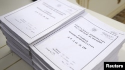Volumes of declassified information lay on a table during the ceremony in Moscow on April 7.