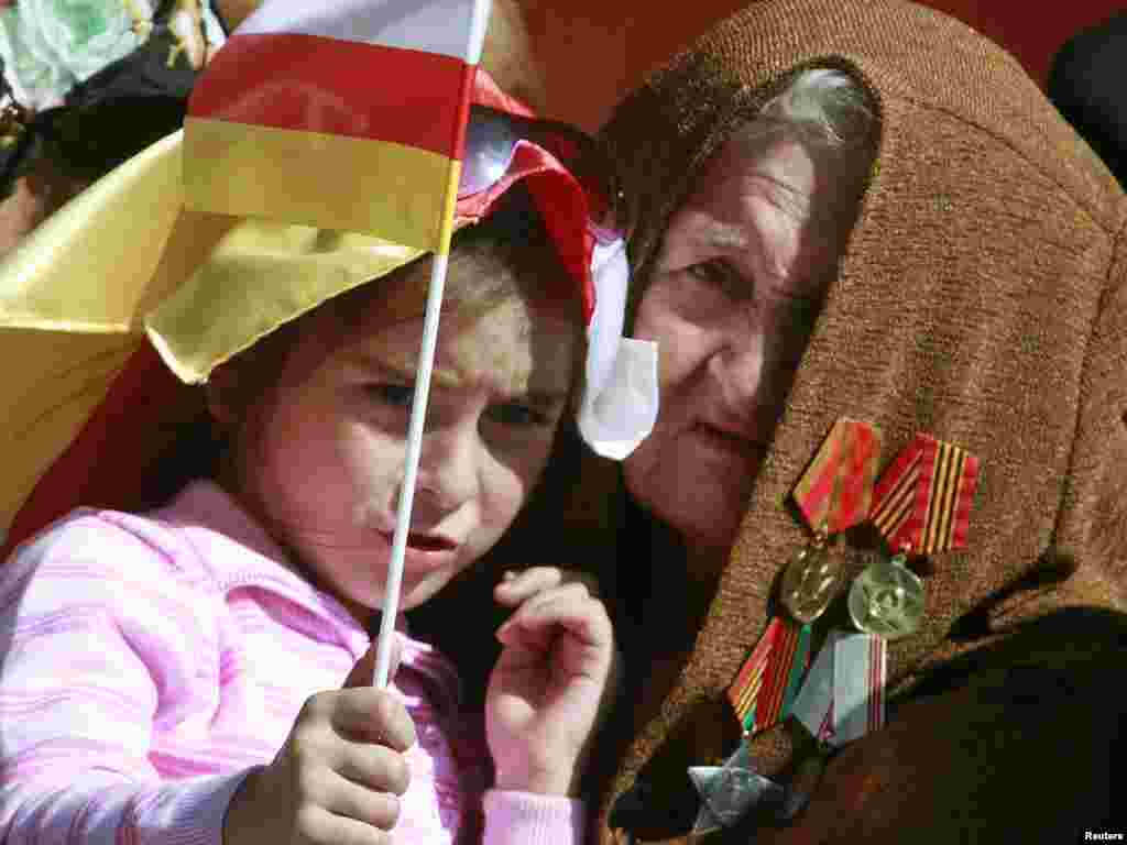 A woman holds a girl with a South Ossetian flag during the Independence Day celebration in South Ossetia's main city of Tskhinvali on September 20. The breakaway region celebrated the 20th anniversary of declaring itself independent from Georgia. Photo by Kazbeg Basayev for Reuters