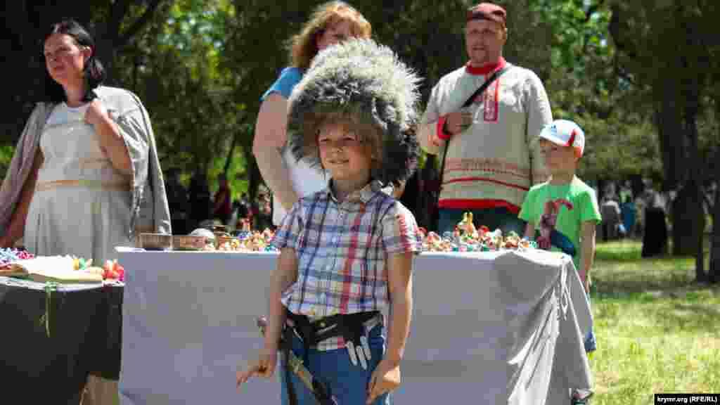 Дети фотографируются в казацких папахах и с оружием