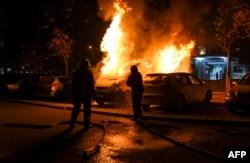Пожежники гасять підпалене демонстрантами авто, Приштина, 18 листопада 2015 року