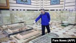 Un angajat sanitar dezinfectează altarul sfântului Masoumeh din orașul Qom