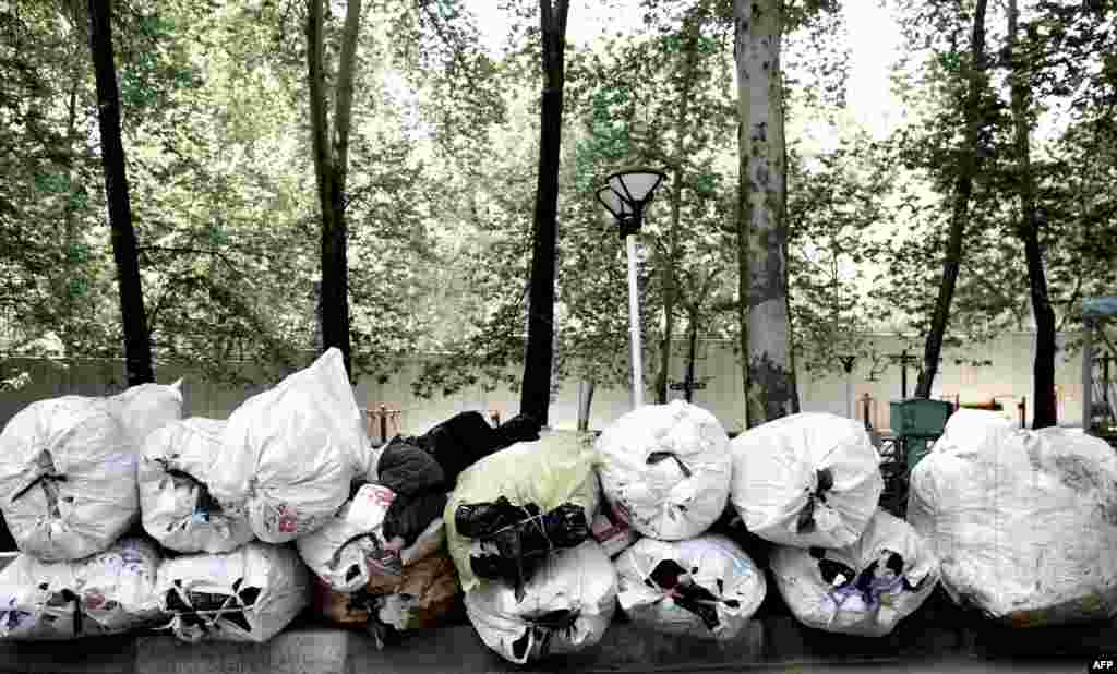 A scavenger sleeps on a pile of items collected from trash bins as he waits for a vehicle to take them for recycling in northern Tehran. (AFP/Behrouz Mehri)