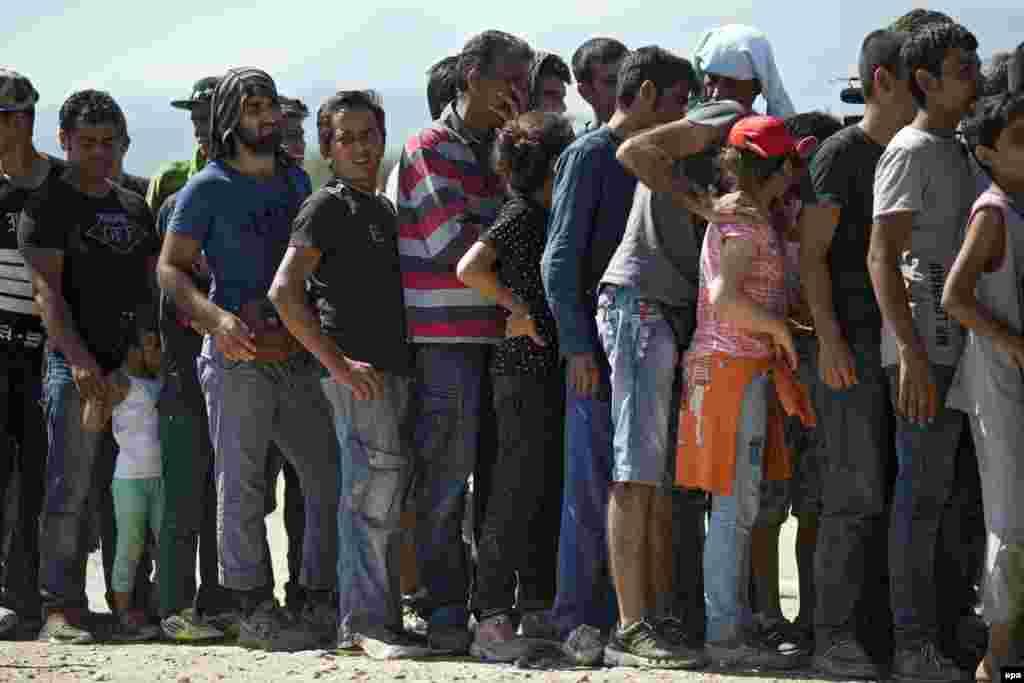 Грекиядан Македонияға өткен босқындар Гевгелия қаласы маңында тамақтың кезегінде тұр.1 қыркүйек 2015 жыл.