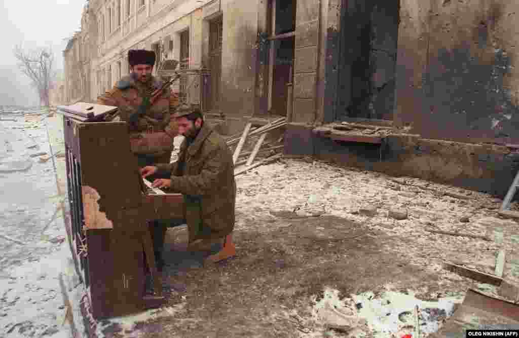 Чеченский боец играет на пианино в центре Грозного. Многие дома в первые дни войны были разграблены военнослужащими федеральных войск, а потом подвергнуты бомбардировке или подожжены. 22 декабря 1994 года