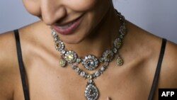 A model poses with a parure of antique colored diamond jewels during a press preview by Sotheby's auction house in Geneva, November 9, 2016
