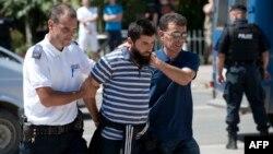 Сириядағы соғысқа қатысқан деген күдіктіні Косово полициясы сотқа әкеле жатыр. Приштина, 12 тамыз 2014 жыл.