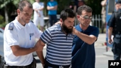 Kosovo police officers escort a man suspected of having fought with Islamist insurgents in Syria and Iraq as they arrive at a court in Pristina on August 12.