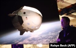 """Илон Маск 7 астронавтты сала алчу жаңы """"Dragon V2"""" космос кемеси тууралуу маалымат берүүдө. 2014-жылдын 29-майы."""
