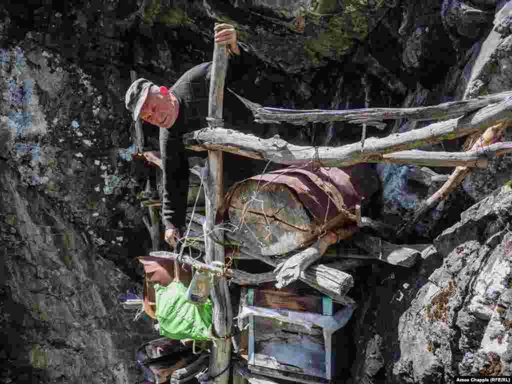 Тамаз Путкарадзе собирает мед из своих ульев на шатком каркасе из дерева и проволоки, который он построил около 20 лет назад в расщелине скалы