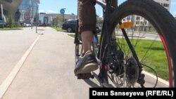 Велосипед теуіп бара жатқан адам. Астана. Тамыз, 2017 жыл.