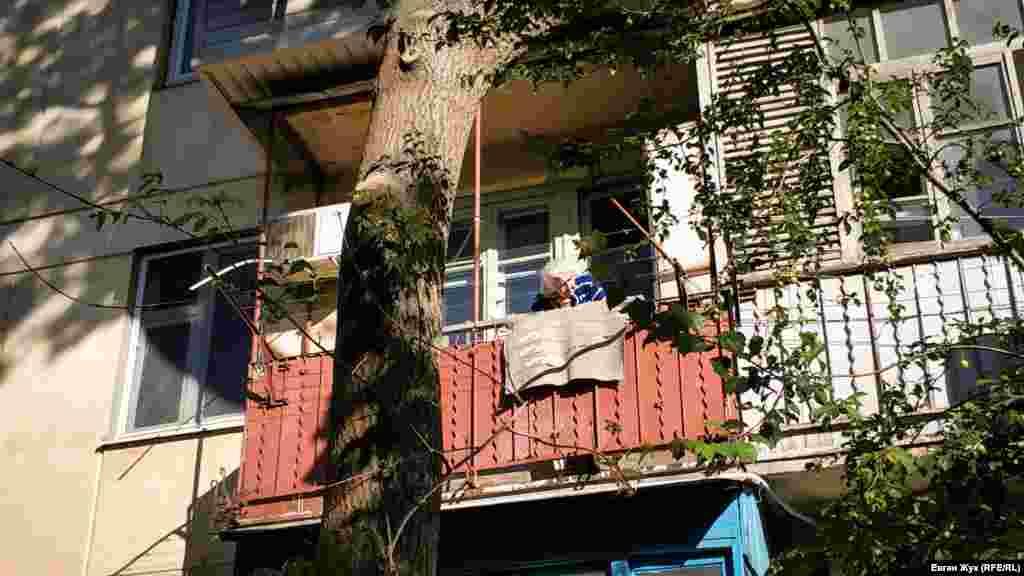 Літня жінка дихає свіжим повітрям на балконі