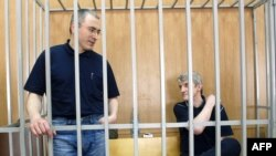 Former Yukos oil company CEO Mikhail Khodorkovsky (left) and Platon Lebedev in a Moscow courtroom -- will they receive more than moral compensation?