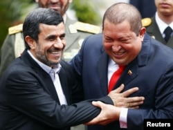 Iran's President Mahmud Ahmadinejad (L) is welcomed by Venezuela's President Hugo Chavez (R) at Miraflores Palace in Caracas, 09Jan2012
