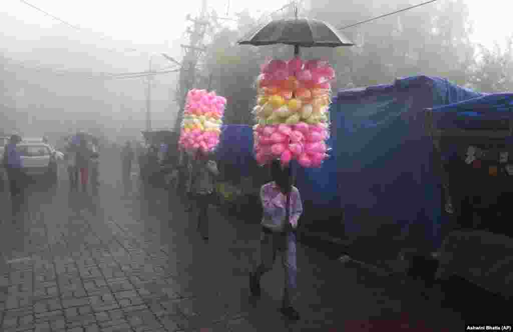 Traveling vendors sell cotton-candy on a foggy day in Dharmsala, India. (AP/Ashwini Bhatia)