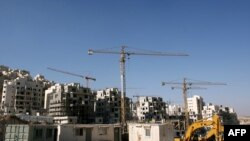 Construction cranes and excavators at the building sites of new housing units in the Jewish settlement of Har Homa in East Jerusalem