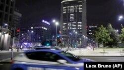 Полицейский автомобиль у здания в Милане, надпись из света окон которого гласит на итальянском: «State a casa» («Оставайся дома»).